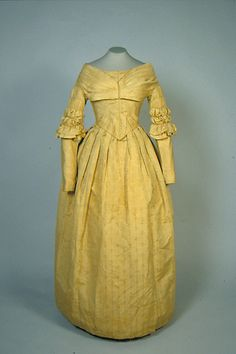 "Dress - late 1830s to early 1840s Gold figured silk dress - internal padding, banded sleeves, hem is 6"" wide, closure of 12 brass hooks and eyes and one metal snap, bodice is lined with brown cotton muslin and sleeves are lined with a finer cotton of the same brown. ATHM"
