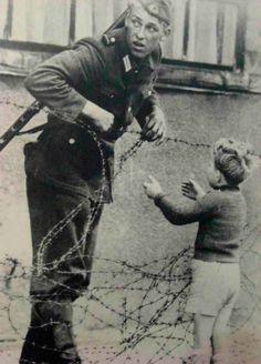 """Un soldado de Alemania Oriental ignora las órdenes de no dejar que pase nadie y ayuda a un niño del lado opuesto a reencontrase con su familia cruzando el """"Muro de Berlín"""". [Guerra Fría, 1961]."""