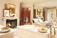 Ralph and Ricky Lauren's country house in Bedford, New York, celebrates classic English style with an American point of view. The couple's stately master bathroom features a fireplace with an 18th-century mantelpiece, and a freestanding marble bathtub. The mirrored wall reflects views of the lush gardens. (November 2004)