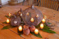 Eine herbstlische Deko wird mit diesen Drahtkürbissen und Kerzen erreicht