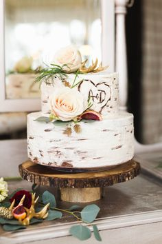 These rustic wedding cakes with flowers, greenery, and fall fruit atop rustic wooden cake stands are the perfect finish to a barn wedding reception or fall wedding.