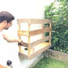 He nails scrap wood into a shed. This shed build-out idea is gorgeous! Building Raised Beds, Shed Building Plans, Building Ideas, Wood Storage Sheds, Wood Shed, Diy Hanging Planter, Wood Planters, Small Shed Plans, Cheap Sheds