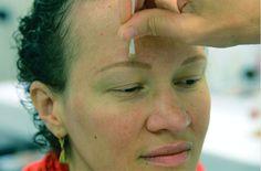 """8. Catalina perdió sus cejas a raíz de los tratamientos, pero no volvieron a crecer. Gracias a una foto, Joelle pudo reajustar la altura y el largo. No va a dibujar exactamente la misma ceja, sin embargo Catalina va a poder reconocerse. Para corregir su dibujo, Joelle va a recurrir a la """"goma"""" del maquillador, es decir a la base de maquillaje. Con un bastoncillo, se aplica en las cejas con el fin de poder volver a redibujarlas."""