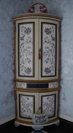 symmetrical painted blue floral on white panels of corner cupboard