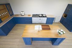 A unique view of one of our kitchens painted in Stiffkey Blue by Farrow & Ball. The rear of the island is recessed for seating a few of your friends or family to make a truly social hub of your home.  www.nakedkitchens.com