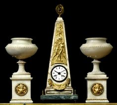"White marble, obelisk-shaped, the bezel with beaded decoration, above the clock an inset gilt-bronze panel depicting two graces uplifting the globe on which Cupid stands holding a flaming torch and bow, below the clock two opposing lions, the sides top and base with gilt-bronze beaded outlining, with armillary sphere finial, on a grey with white veins marble base; together with a matching pair of tazzas with ormolu lions heads on base. Similar clock represented in Tardy's ""La Pendule…"