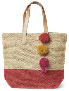 Coral Montauk Carryall Bag – Favery -- Perfect for the beach, the market, or zipping around town, this beautiful carryall bag, crocheted from sustainable sisal with a classic stripe, is adorned with festive raffia pom poms and features a cotton lining, snap closure, and durable leather handles.