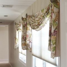 These side by side windows in an upstairs hallway are decorated with scarf swags in a multi colored floral print with tassel trim.  Hunter Douglas honeycomb shades protect a large painting in the stairwell from UV rays.  Scarf swags made by Curtain Call.