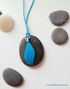 """Colgante """"Ligero como pluma"""" azul III.  Piedra natural pulida por el mar, cogida en la playa, agujereada a mano, decorada con plumita y colgada en cordón.  #piedra #pluma #hechoamano #azul #natural #playa"""
