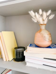 Arranging a bookshelf to look HGTV-perfect is tough. But I've found putting some small fried flowers like these bunny tails to instantly level-up any shelf.