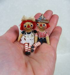 Miniature Raggedy Ann and Andy dolls.