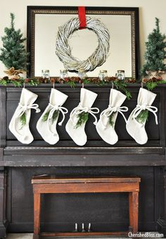A Rustic Christmas Mantel featuring real cedar garland and drop cloth stockings. No fireplace mantel? Use an upright piano to decorate for the seasons.
