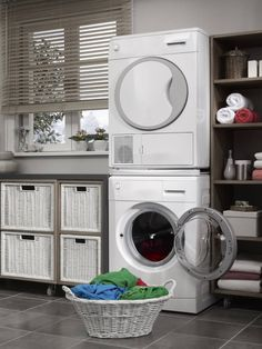 A laundry room with cube storage and white wicker drawers. All of the storage is on wheels for easy rearrangement. The washer and dryer are stacked to conserve space.