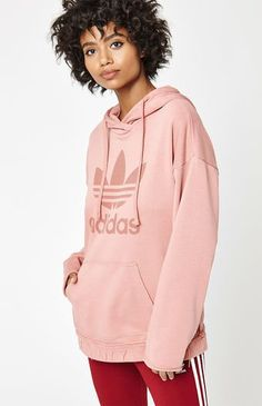 Maintain your sporty and casual style with the classic Pink Trefoil Hoodie by adidas. This essential pullover hoodie boasts a large Trefoil logo at the chest, hood with drawstring, distressed detailing at the band, and front pockets.    Pullover hoodie  Long sleeves  Drawstring hood  Trefoil logo graphic  Pouch pocket  Model is wearing a small  70% cotton, 30% polyester