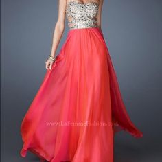 """La Femme prom/formal/pageant dress style 18602 La Femme prom dress style 18602, size 0, altered to fit 32"""" bust, 25"""" waist, 5'5"""" and wore with 3"""" heels. Beautiful dress made of lightweight coral material, gold/silver strapless top with gems and cutouts, small train. Wore one time for prom, purchased for $425, selling for $325 but willing to sell for lower if you make an offer La Femme Dresses Strapless"""