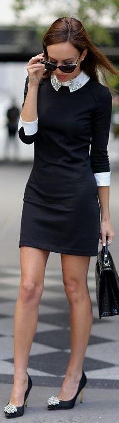 Black sheath dress with white embellished collar and white cuffs, black heels, and black handbag