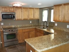 light maple cabinets with chocolate glaze and santa cecelia granite counters