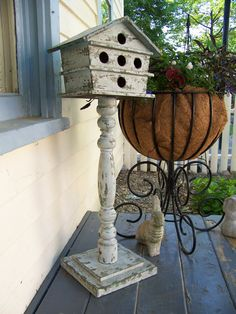 Love this weathered birdhouse sitting on a stair bannister and two pieces of cut wood...so cute!!