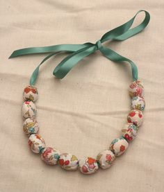 Fabric covered bead necklace with ribbon tie.