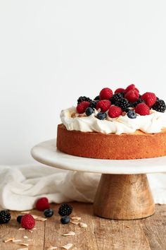 An EASY Lemon Coconut Cake topped with lightly sweetened whipped cream and fresh mixed berries. This simple celebration cake for Easter or springtime is elegant, flavorful, and comes together quickly.