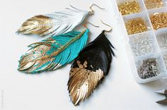 Leather Feather Earrings with Gilded Golden Tips  Feather plumes dipped in gold dangle from your lobes. These earrings sparkle and illuminate when the light hits them.   etsy.com