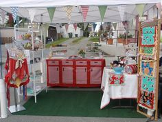 White wire rack shelving?  Vintage table cloths. Buntings.    Booth set up by Home Deconomics, via Flickr
