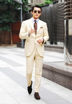 Light beige suit, light blue shirt, brown tie