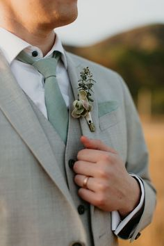 Groom wearing a grey suit with a succulent boutonniere and eucalyptus mint green tie also sporting a hammered rose gold wedding ring. Green Wedding Suit, Wedding Tux, Sage Green Wedding, Gold Wedding, Wedding Table, Wedding Groom Attire, Grey Tuxedo Wedding, Summer Wedding, Dream Wedding