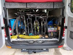 The back of the van is where the bikes live. But they have to play nice and share that space with our bed, the battery and electrical control panel, the water tank, and the shower hose. Van Storage, Bike Storage, Storage Spaces, Van Conversion Cabinets, Plastic Wall Panels, Shower Hose, Sprinter Van, Water Tank, Interior Walls