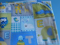 Baby blanket blue with baby animals and letters on one side and the other side is blue gray yellow.Blanket is lined with a decorative stitch by MissyCraftsandGoods on Etsy