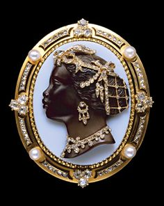 Onyx cameo head of a negress facing in profile towards the left, magnificently habillee in gold and rose diamond jewels like an Empress diamond necklace fringed with drop shaped pendants, huge gold crescent and girandole earring, bandeau tied with a knot over brow with plume linked by festoon chains and pendants to jewelled net over chignon at the back of the head...