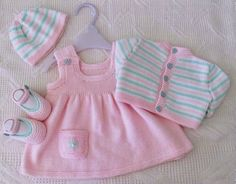 Cute baby knitwear ensemble. Beautiful baby girl knitting set with dress cardigan shoes and hat.