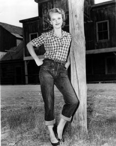 1954-1964 fashion. New look. This is a photograph of a woman.This would be a typical outfit women would wear for house work. She is wearing pedal pushers with a plaid short sleeved shirt that is tucked into the pants with flat shoes that are easy to walk around in. Plaid became very popular.