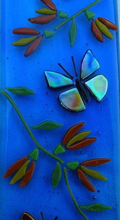 This is an fused glass art picture of butterflies and flowers on a blue glass background. The butterflies are made with dazzling dichroic glass. This is an original signed piece of art. This piece of glass art measures 8cm x 19cm Made by me in my Sussex Studio.