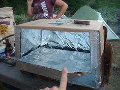 Home made pizza oven while camping. Box lined with foil and placed on camping stove.