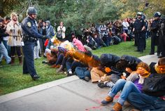 """A University of California Davis police officer pepper-sprays students during their sit-in at an """"Occupy UCD"""" demonstration"""