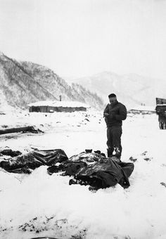A wounded chaplain reads a memorial service over the snow-covered bodies of dead Marines. Koto-ri, Korea. December 3, 1950. Cpl. W. T. Wolfe. (Marine Corps)NARA FILE #: 127-N-A5552WAR & CONFLICT BOOK #: 1512Cleared for public release. This image is generally considered in the public domain - Not for commercial use.U.S. Army Korea - Installation Management Command
