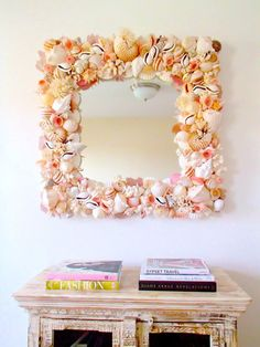 A beautiful mirror for your home featuring many types of premium quality seashells and coral pieces in shades of soft beige, white and pink. I started with a white clam shell base which you can see on the inside of the mirror I next placed the four creamy white Whelk shells at each corner. From there I meticulously fit the rest of the shells in place. This takes a lot of time and a lot of shells. : ) However the end result is just lovely. The large nautilus shells are holding beautiful…