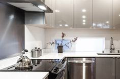 Shiny grey cabinets help bounce light around the space