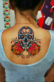 A colorful sweet sugar skull tattoo on the back with flowers