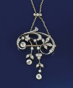 An Art Nouveau diamond pendant necklace  The pendant with old-cut diamond floral scroll surmount suspending graduated twin floral design drops with old brilliant-cut diamond collet teminals, to a trace link neckchain with diamond three stone accent, mounted in silver and gold, circa 1895, pendant detachable for wear as a brooch