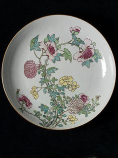 Porcelain dish painted in polychrome enamels of the famille rose colour scheme with branches of peonies and chrysanthemums that run over the side of the dish and on the back; an inscription in ink on the base.Qing dynasty, Yongzheng reign, ca.