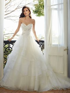 Yards of organza span the ballgown silhouette of Sophia Tolli Y11565 Egret Wedding Dress, embellished with light beadwork accentuating the ruched surplice bodice. The strapless sweetheart neckline leads into the corset back, which tapers the bodice into the natural waist. From there, the shirred tiers of organza cascade down the floor with a chapel train. Set includes removable spaghetti and halter straps.