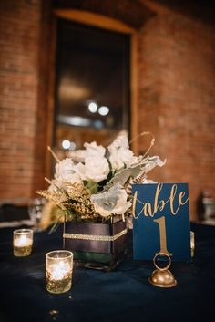 This winter wedding table number style blends perfectly with center pieces. Love the gold and navy color scheme