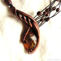 Baltic amber in a wooden frame. Hand carved pendant hung on a leather thong. Unique jewelry by Aneta Majzner