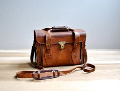 Genuine leather vintage camera bag with sturdy brass hardware and white…