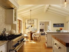 Love the use of large art work on the wall and the wood island mixed with the marble on the counters