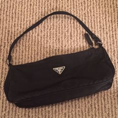 Authentic Prada nylon bag Authentic Prada black bag. Worn. The bag is nylon material and is in decent condition; some spots on the inside. It's 9.5 inches long and 4 inches in height. ⚠️❌The handle is very worn. The bag handle needs to be replaced and the bottom of the bag is also a little worn. See image 3. ❌⚠️ offers accepted  all my items come from a smoke free home. Prada Bags Mini Bags