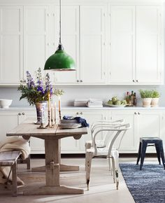 Rustic chic.  Green pendant lamp.  White on white.  Tall cabinetry, small space between cabinets and kitchen counter.  Mismatched dining room furniture.  Vintage, distressed metal chairs.