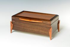 A handcrafted wood box to serve many purposes. The box is made of tropical Peruvian Walnut. The contrasting lid is ribbon Sapele veneer. the legs, the contrasting corner accents and handle are genuine Mahogany. Hinges are solid brass quadrants with stops that hold the lid open. Inside, the